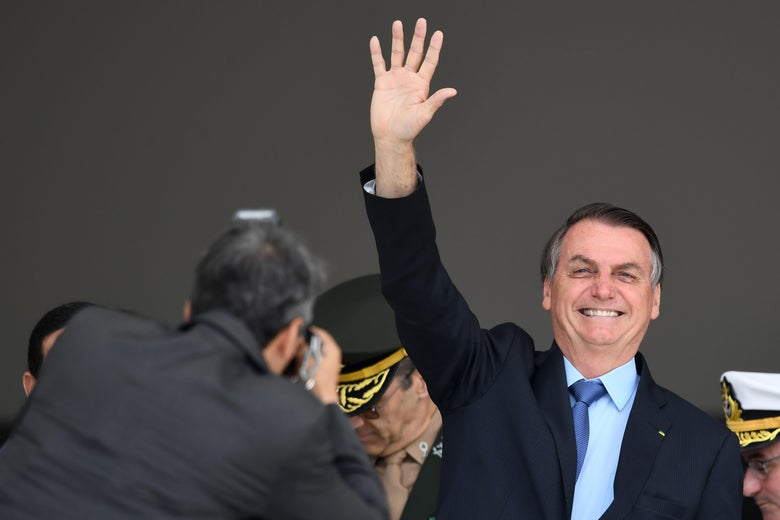 Brazilian President Jair Bolsonaro waves during the presidential guard change ceremony at Planalto Palace in Brasilia, on November 28, 2019.