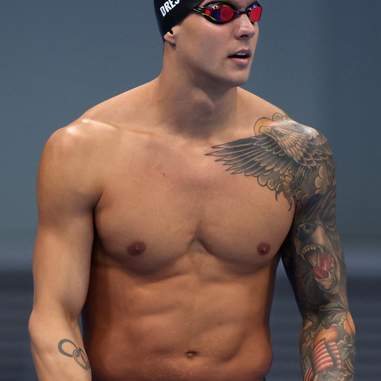 Dressel in goggles and swim cap, his left arm covered in the eagle, bear, oranges, and flag tattoo described below, a small Olympics rings tattoo visible as well on his right forearm