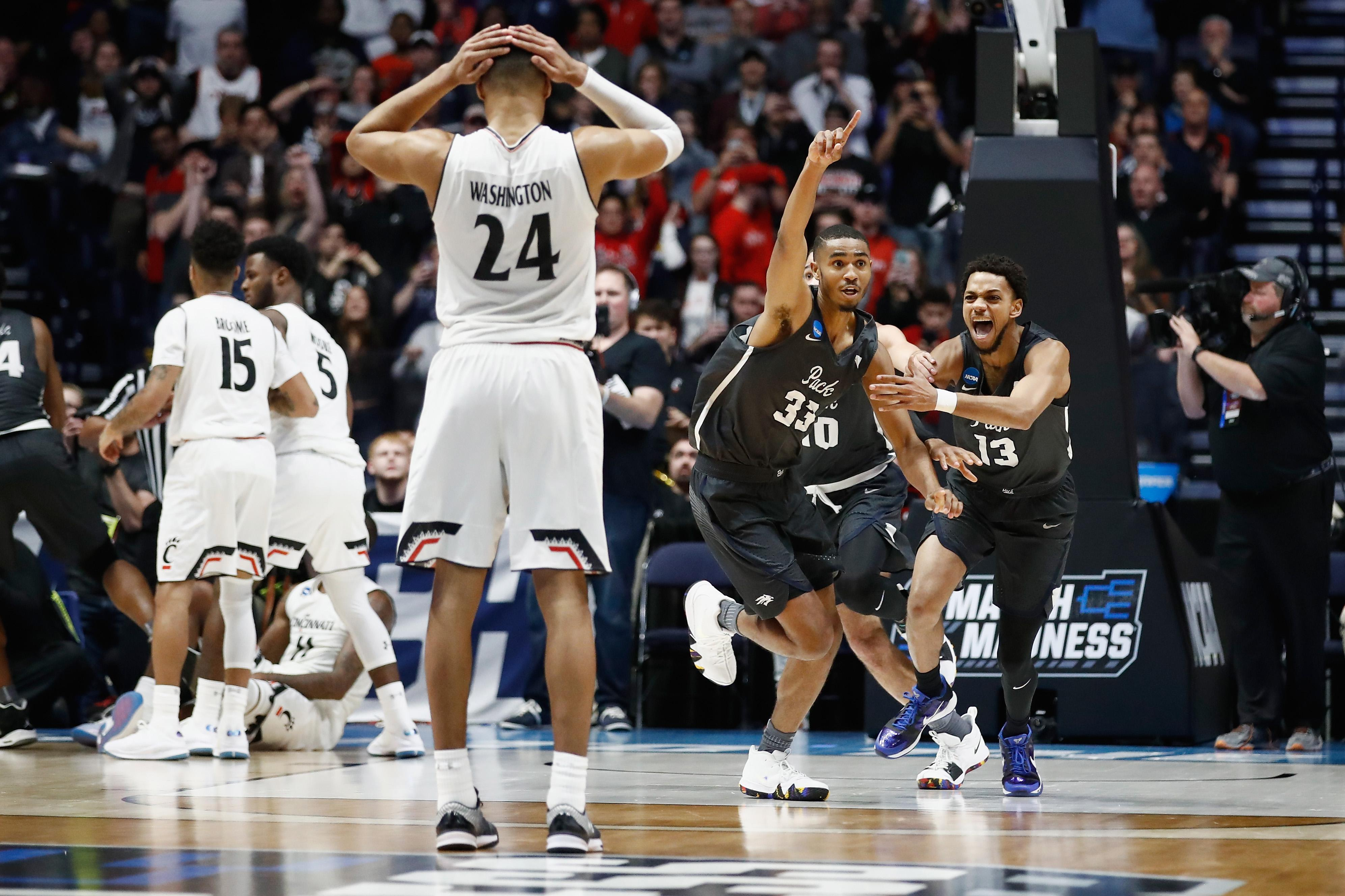 NASHVILLE, TN - MARCH 18: Josh Hall #33 of the Nevada Wolf Pack celebrates with Hallice Cooke #13 after defeating the Cincinnati Bearcats during the second half in the second round of the 2018 Men's NCAA Basketball Tournament at Bridgestone Arena on March 18, 2018 in Nashville, Tennessee. (Photo by Andy Lyons/Getty Images)