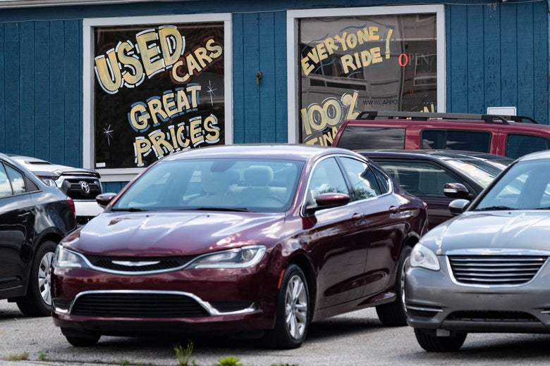 """A used car delership is seen in Laurel, Maryland, with a window sign that says, """"Used Cars. Great Prices."""""""