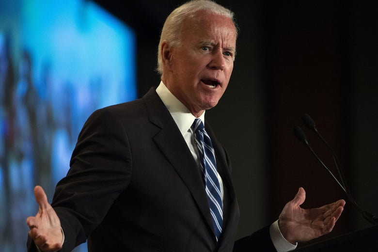 Joe Biden shrugs while speaking at a podium.
