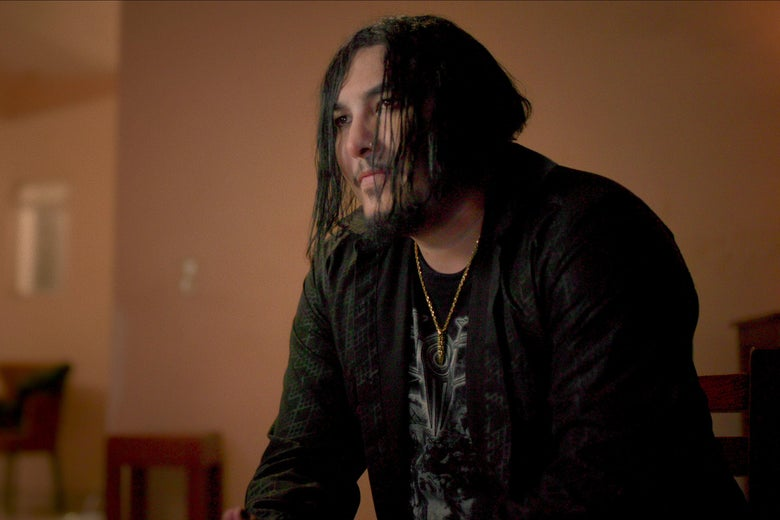 A man sits with long stringy dark hair hanging over his goateed face