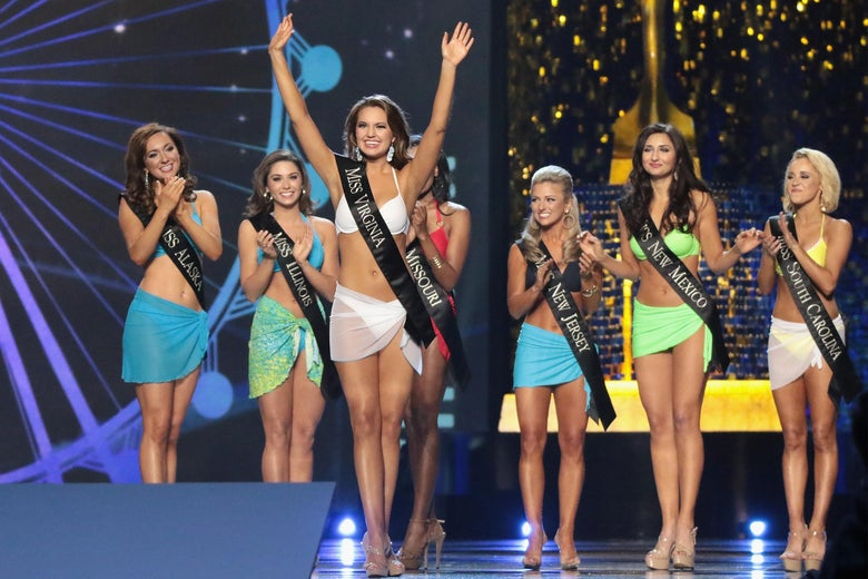Miss Virginia waves to the crowd while wearing a white bikini. Other Miss American contestants applaud behind her, all while wearing swimsuits.