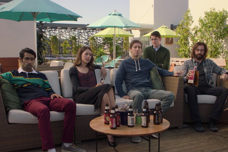 The cast of HBO's Silicon Valley sitting on outdoor furniture on a rooftop. They all look depressed, and Martin Starr is holding a full bottle of tequila.
