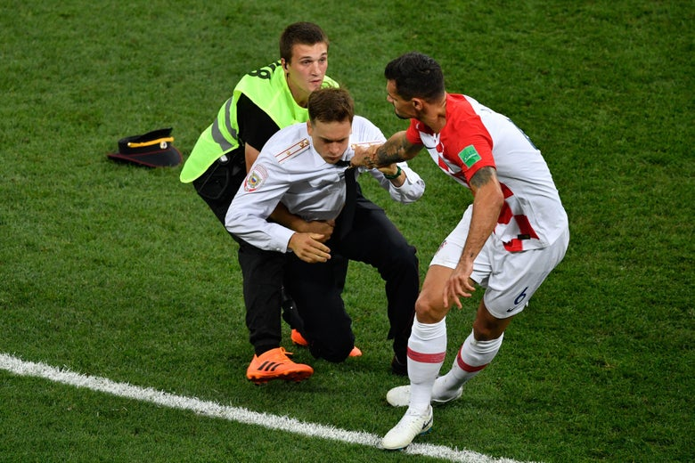 A protester is evacuated from the football pitch by security guards and Croatia's defender Dejan Lovren during the Russia 2018 World Cup final football match between France and Croatia at the Luzhniki Stadium in Moscow on July 15, 2018.