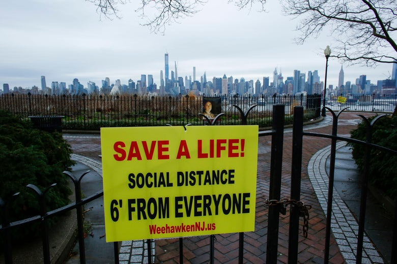 A Newly installed sign encouraging social distancing to stop the spread of the coronavirus (COVID-19) is displayed on a closed park as the skyline of Manhattan is seen From Weehawken New Jersey on March 28, 2020.