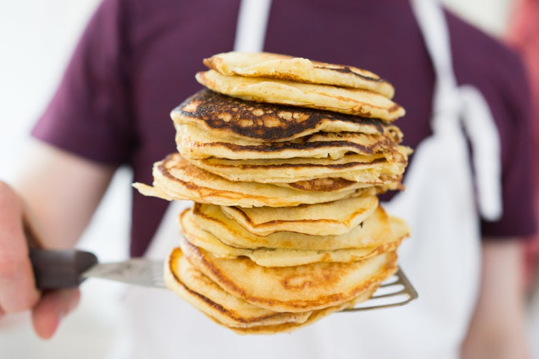 man holding a stack of pancakes on the spatula