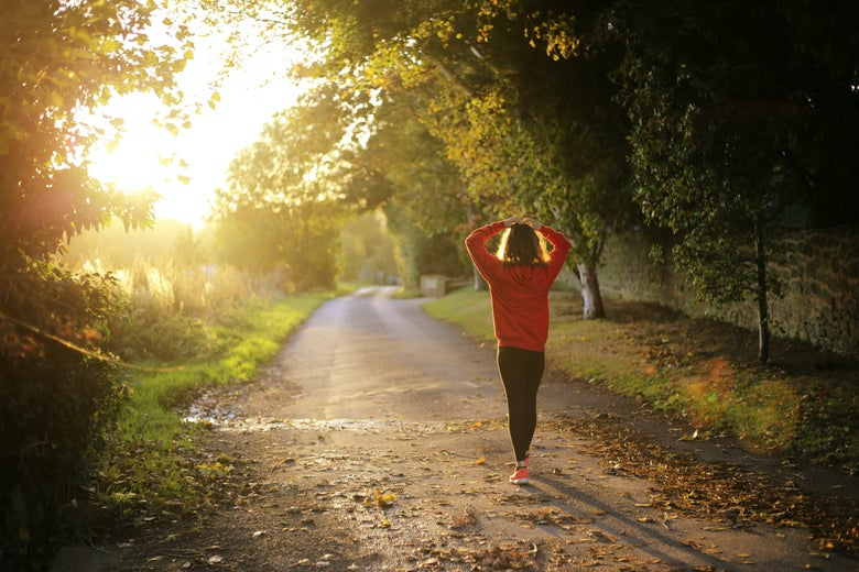 Woman walking with her hands on her head down a sunlit pathway with trees on either side