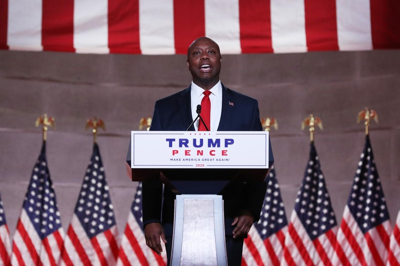 """Tim Scott speaks at a podium with a """"Trump Pence"""" sign on it. Behind him are American flags."""