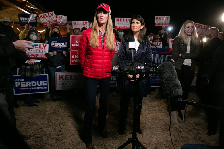 Haley, wearing a blue jacket, watches while Loeffler speaks to reporters in front of a crowd of supporters.