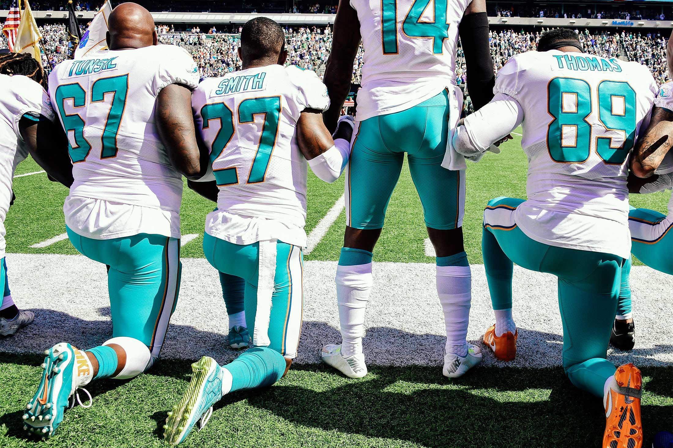Miami Dolphins Laremy Tunsil, Maurice Smith, and Julius Thomas kneel as Jarvis Landry stands on the sidelines.