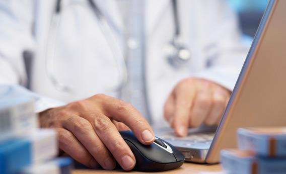 A doctor on a computer.