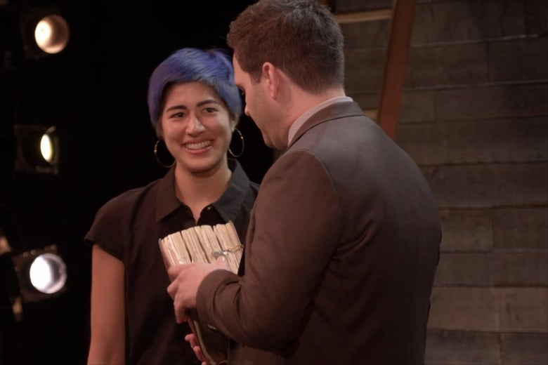 Emma Sulkowicz hands a large book to Derek DelGaudio.
