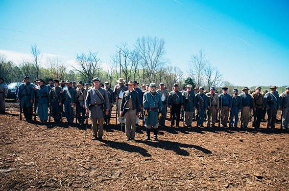 "A large group of Confederate re-enactors face inspection from their ""officers"" before a march."