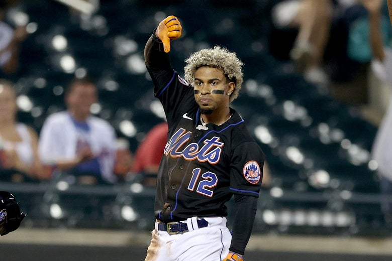 Lindor with his helmet off giving a thumbs-down with his right hand and frowning