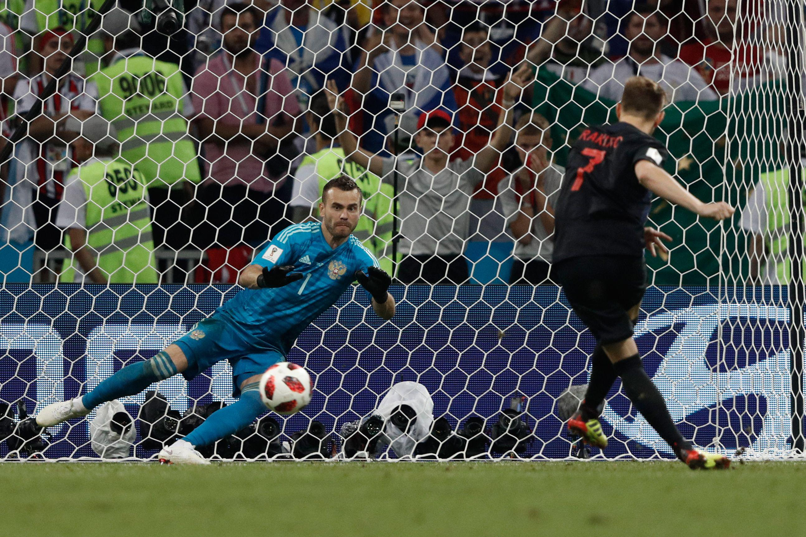 Croatia's midfielder Ivan Rakitic (R) scores his penalty past Russia's goalkeeper Igor Akinfeev during the Russia 2018 World Cup quarter-final football match between Russia and Croatia at the Fisht Stadium in Sochi on July 7, 2018. (Photo by Adrian DENNIS / AFP) / RESTRICTED TO EDITORIAL USE - NO MOBILE PUSH ALERTS/DOWNLOADS        (Photo credit should read ADRIAN DENNIS/AFP/Getty Images)