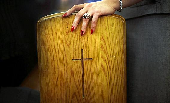A Christian women holds onto a pew.