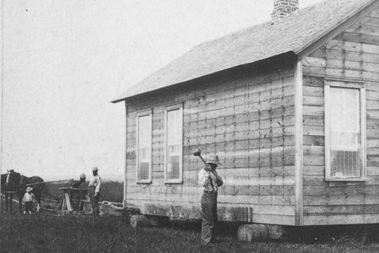 A man stands beside a house on a large cart.