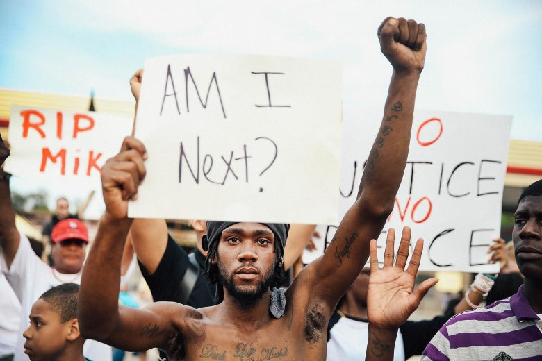 "A man holds up a sign that says, ""Am I next?,"" amid a crowd of protesters."