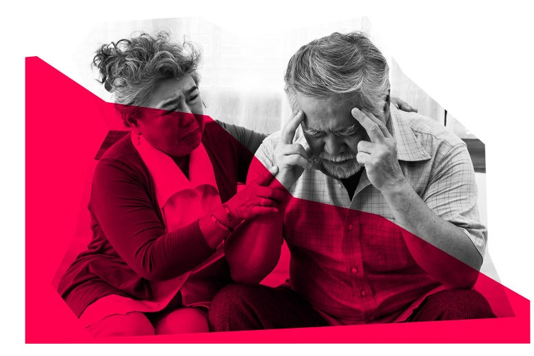 An older woman touches the arm of an older man who is holding his temples and looking distressed.