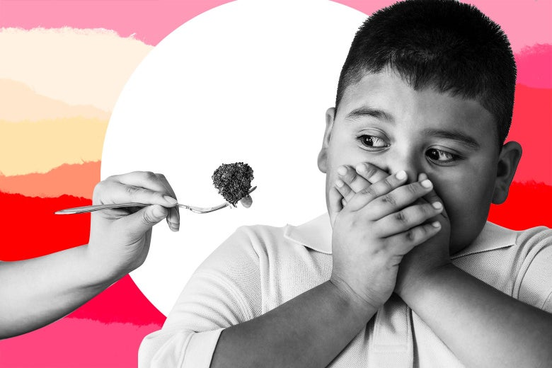 A boy covers his mouth with both hands as another hand proffers a fork with broccoli on it.