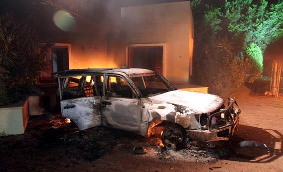 A vehicle and surrounding buildings smolder after they were set on fire inside the US consulate.