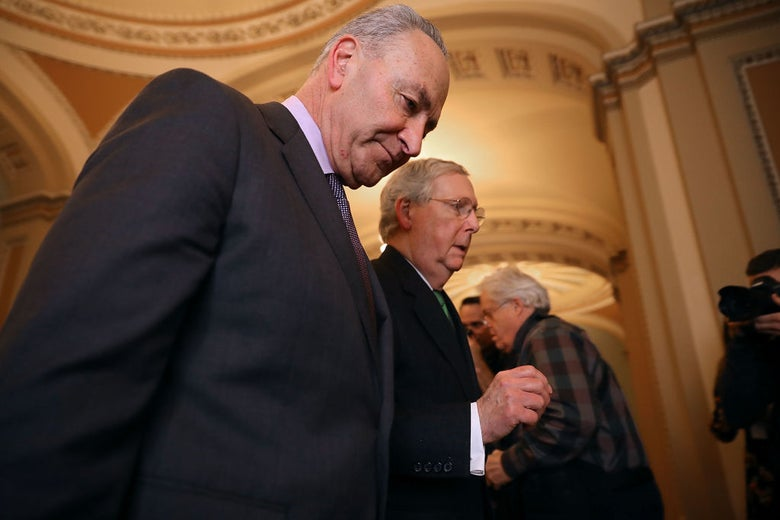 Schumer and McConnell walk side by side as McConnell speaks.