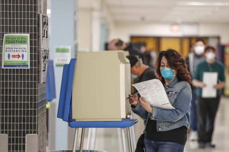 A woman wearing a mask looks at her ballot, with other voters wearing masks in the background