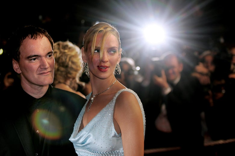 Quentin Tarantino and Uma Thurman stand on a red carpet. In the background, a photographer's bulb flashes.