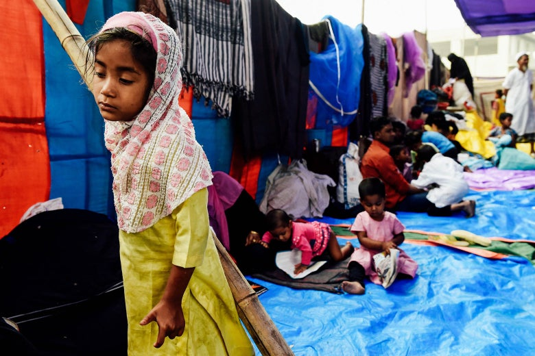 A Rohingya refugee girl looks on at a temporary shelter in New Delhi on Monday, following a fire that broke out at their camp early Sunday that left about 200 people homeless.