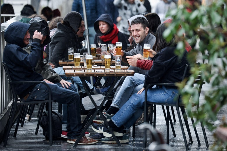 Friends sit at a table drinking beer on a terrace.