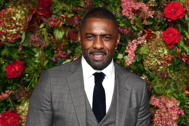 Idris Elba smiles in a grey tuxedo as he poses in front of a wall of prink and red flowers.