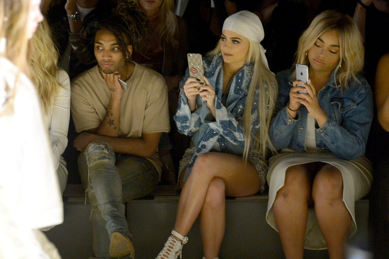 Kylie Jenner (C) and Jordyn Woods (R) sit front row at a fashion show, both taking pictures on their phone