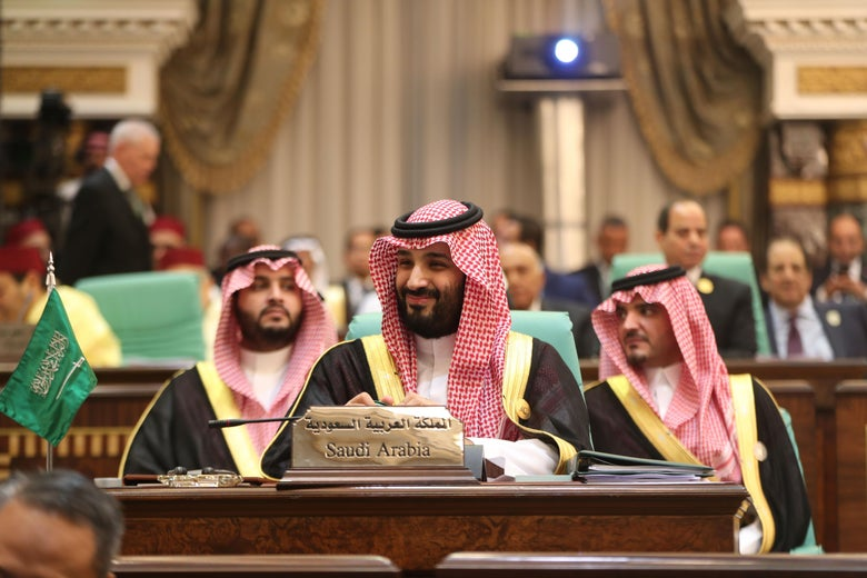 A smiling Mohammed bin Salman sits at a conference table.