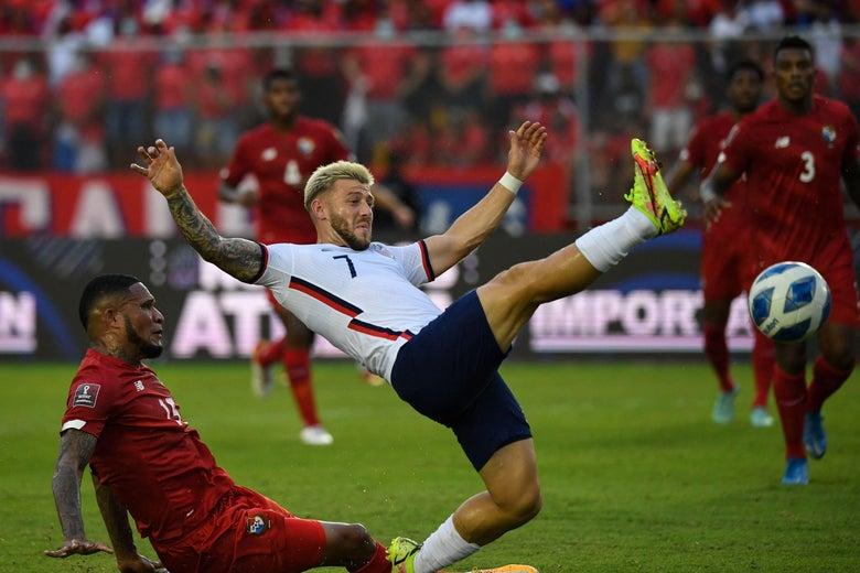 U.S. soccer player Paul Arriola kicks his leg up high as he slips and falls.