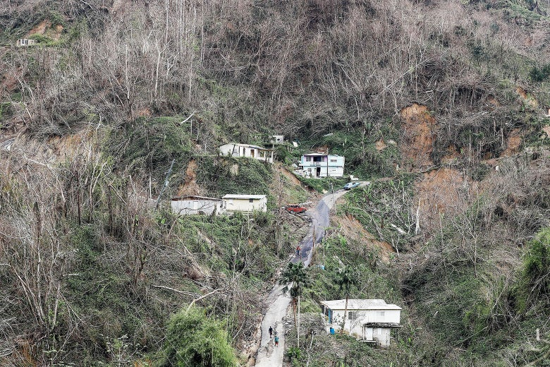 Community members walk on the street in a devastated section nearly three weeks after Hurricane Maria hit the island, on Oct. 10, 2017, in Pellejas, Adjuntas municipality, Puerto Rico.