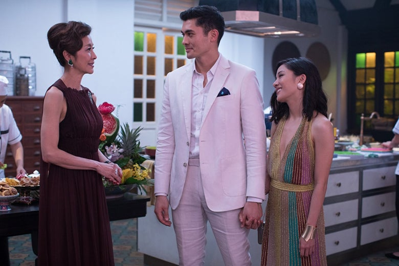 Michelle Yeoh smiles politely at Henry Golding and Constance Wu in a still from Crazy Rich Asians.