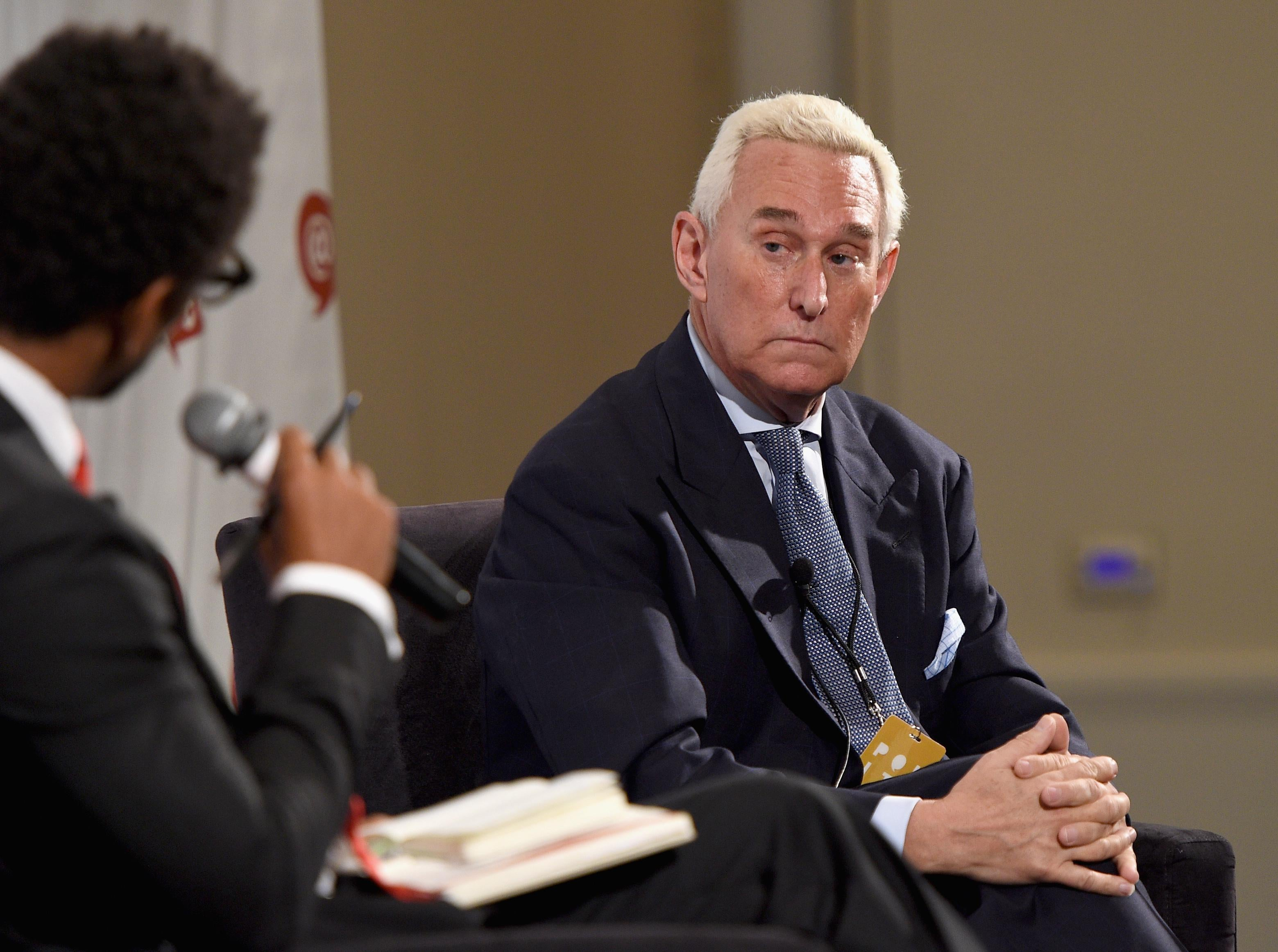 Roger Stone looks warily toward an interviewer holding a microphone.