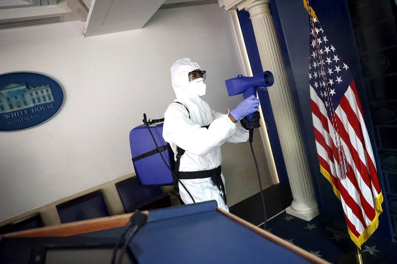 A person in a white full-body protective suit cleans the briefing room.