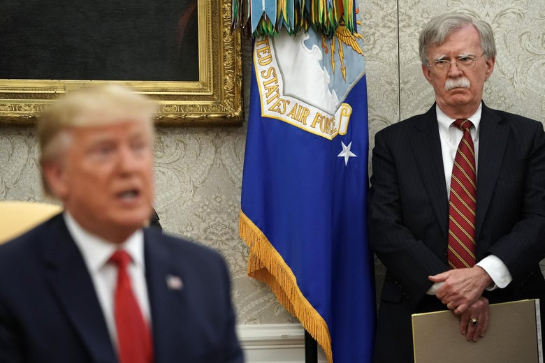 Former White House National Security Advisor John Bolton stands behind President Trump in the Oval Office.