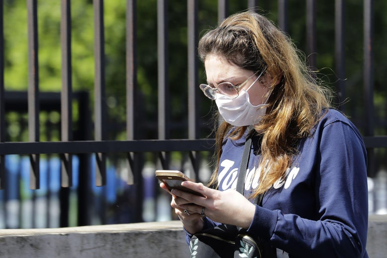 A woman wearing a surgical mask checks her phone, holding it with two hands.