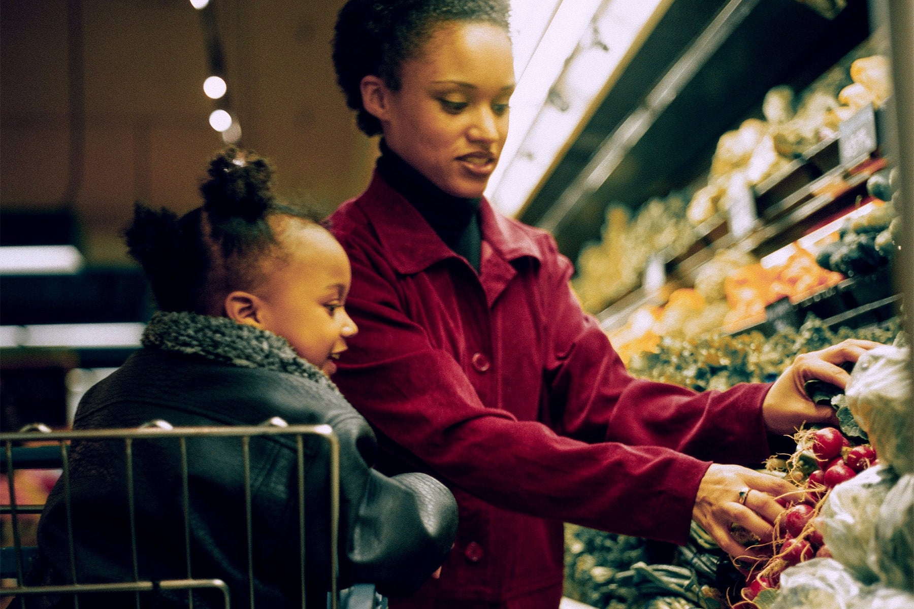 Black woman and child grocery shopping in produce section.
