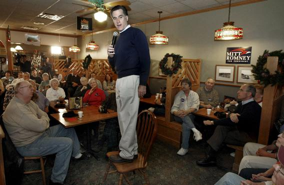 itt Romney (C) speaks to a group of supporters while standing on a chair at Happy Joe's in Clinton, Iowa, USA