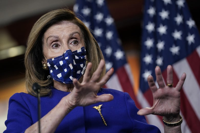 Nancy Pelosi, wearing a face mask and standing in front of two U.S. flags, gestures with her hands.