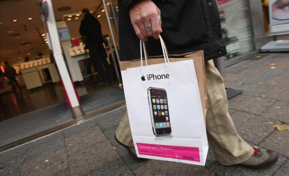 A customer leaves with a just-purchased Apple iPhone at a T-Mobile.