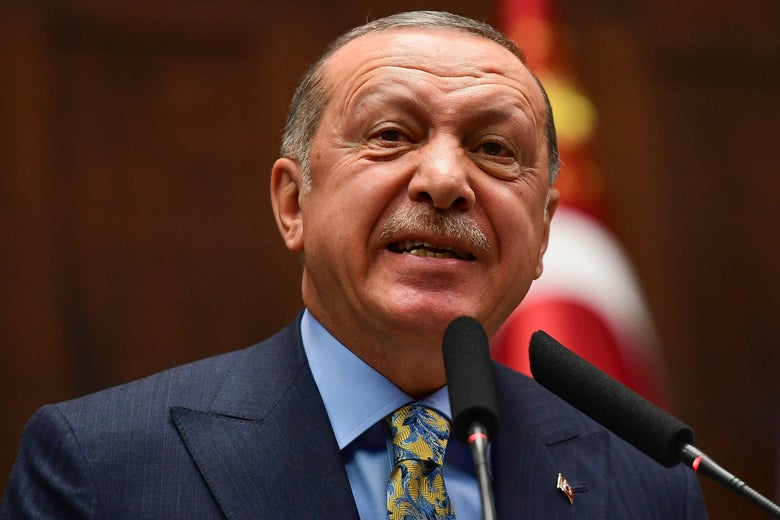 A close-up of Erdogan speaking in front of two microphones at the Parliament.