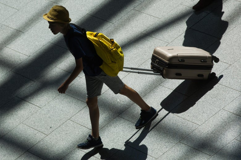 A youth pulls his suitcase at an airport.