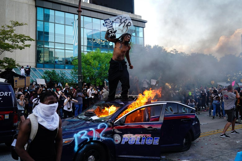A man stands on top of a burning police car during a protest on May 29, 2020 in Atlanta, Georgia.
