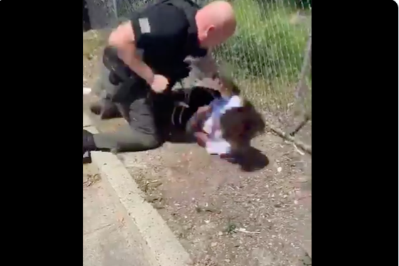 A police officer winds his fist to punch a 14-year-old boy lying on the ground.
