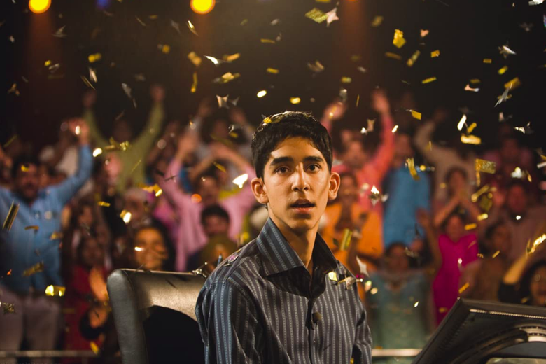 Dev Patel looks directly into the camera, confetti raining down as a crowd cheers behind him.